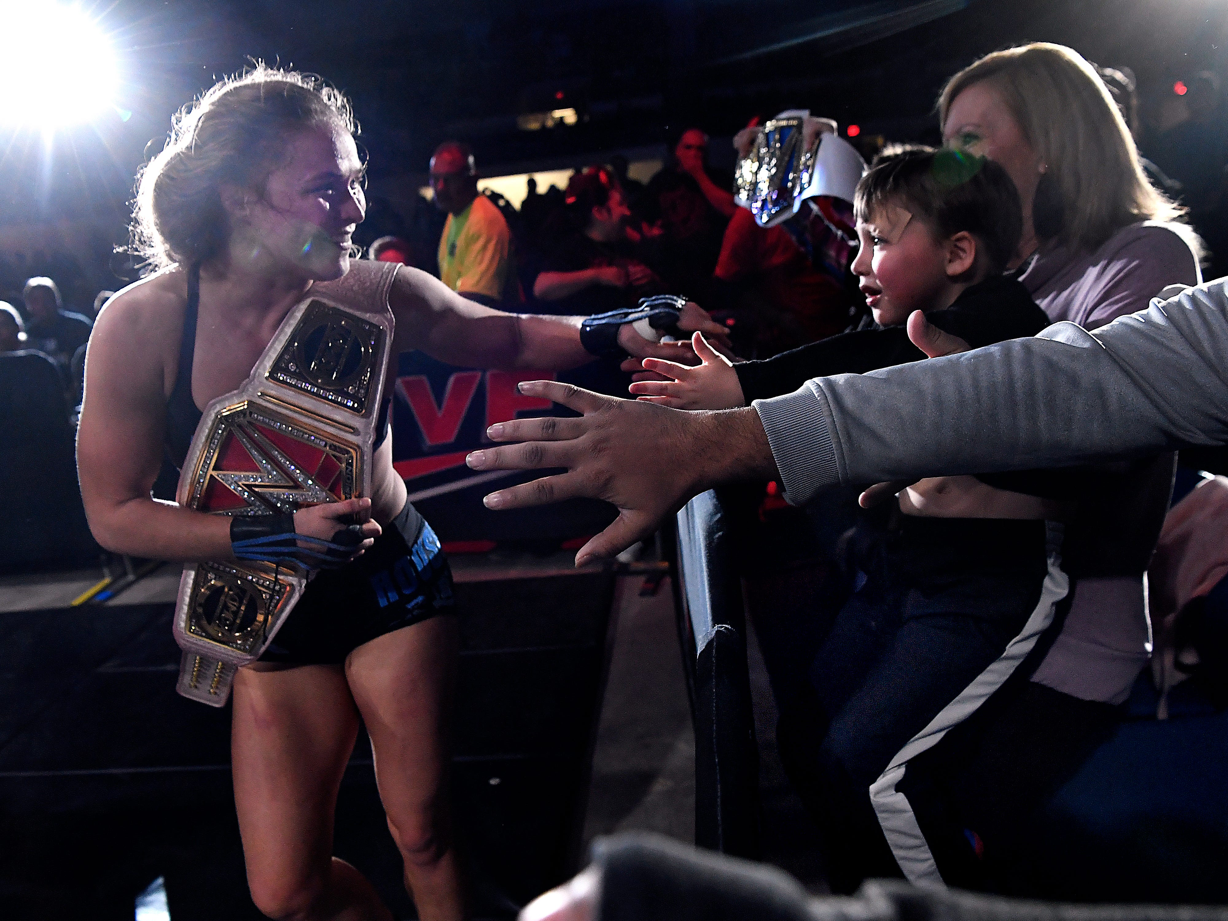 Ronda Rousey briefly takes the hand of four-year-old Weldon Samford, sitting on the lap of his mother Tammy, after her match during Saturday's WWE Live wrestling event Jan. 19, 2019. Held at the Taylor County Coliseum, the evening featured a colorful array of World Wrestling Entertainment stars.
