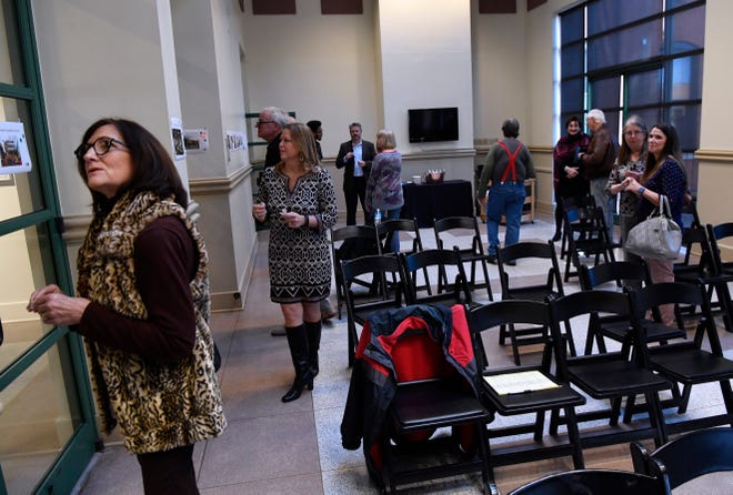Audience members survey printed pictures of different design features during a presentation on libraries Jan. 16, 2019 at The Grace Museum.
