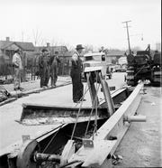 "This snapshot, taken on Patton Avenue in March 1942, comes with the note, ""Here, in Asheville, North Carolina, a local inventor demonstrates his 'railjerk,' a device, employing three men, that can pry loose a mile of track a day."""