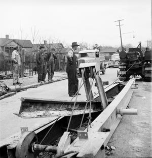 """This snapshot, taken on Patton Avenue in March 1942, comes with the note, """"Here, in Asheville, North Carolina, a local inventor demonstrates his 'railjerk,' a device, employing three men, that can pry loose a mile of track a day."""""""