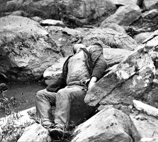 """The Civil War increased death, grief, antagonism and resentment at home and far from home, as represented by this photograph by Timothy H. O'Sullivan, """"Gettysburg: Fallen Confederate on Slaughter Pen boulders,"""" owned by the Library of Congress.The Union photographer only took pictures of Confederate dead."""