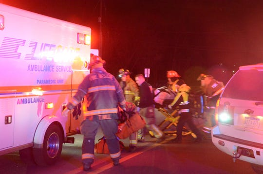 Rescue workers taken one of the injured girls to an ambulance after the Friday crash.