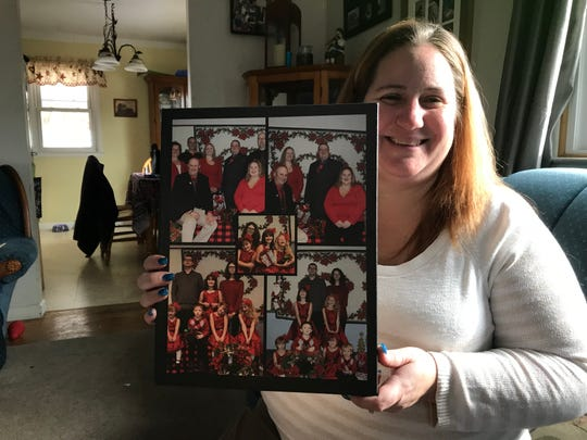 Heather Bodine holds a photo of her siblings, nieces and nephews.