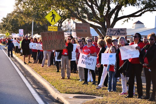 Hundreds of the Brevard Federation of Teachers union members picket outside the school board headquarters to protest low wages.