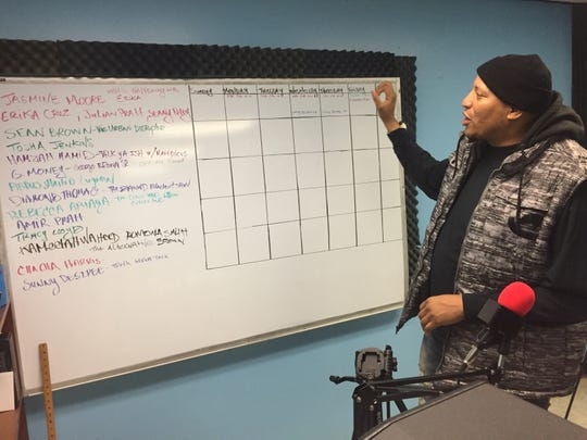 Diamond Thomas shows a whiteboard with some of the podcast hosts he's booked for shows on WCMD.