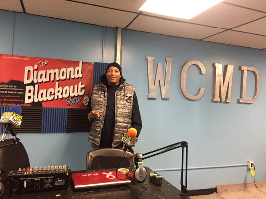 Diamond Thomas stands behind the board at WCMD, a radio studio in Camden's Parkside neighborhood.
