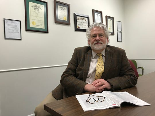 Ross County Coroner Dr. John Gabis sits in his office on Delano Avenue in front of his Paint Valley ADAMH Advocate of the Year award from 2013 and a certificate of accreditation from the International Association of Coroners and Medical Examiners. At the end of January, Gabis will be retiring as coroner after 26 years.