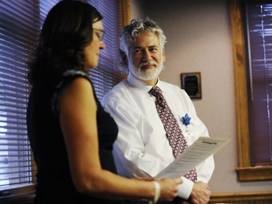 Ross County Coroner Dr. John Gabis listens and smiles as a proclamation is read about him being awarded Advocate of the Year from the Paint Valley ADAMH Board in October 2013.