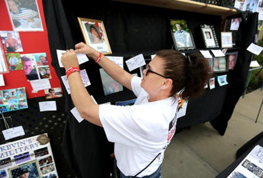 Kimberly Wright of Taylor Mill, Kentucky,  fashions a memorial for a NKY Hates Heroin 5K run. Wright is a treatment advocate who founded the support group Kentucky Parents Against Heroin.