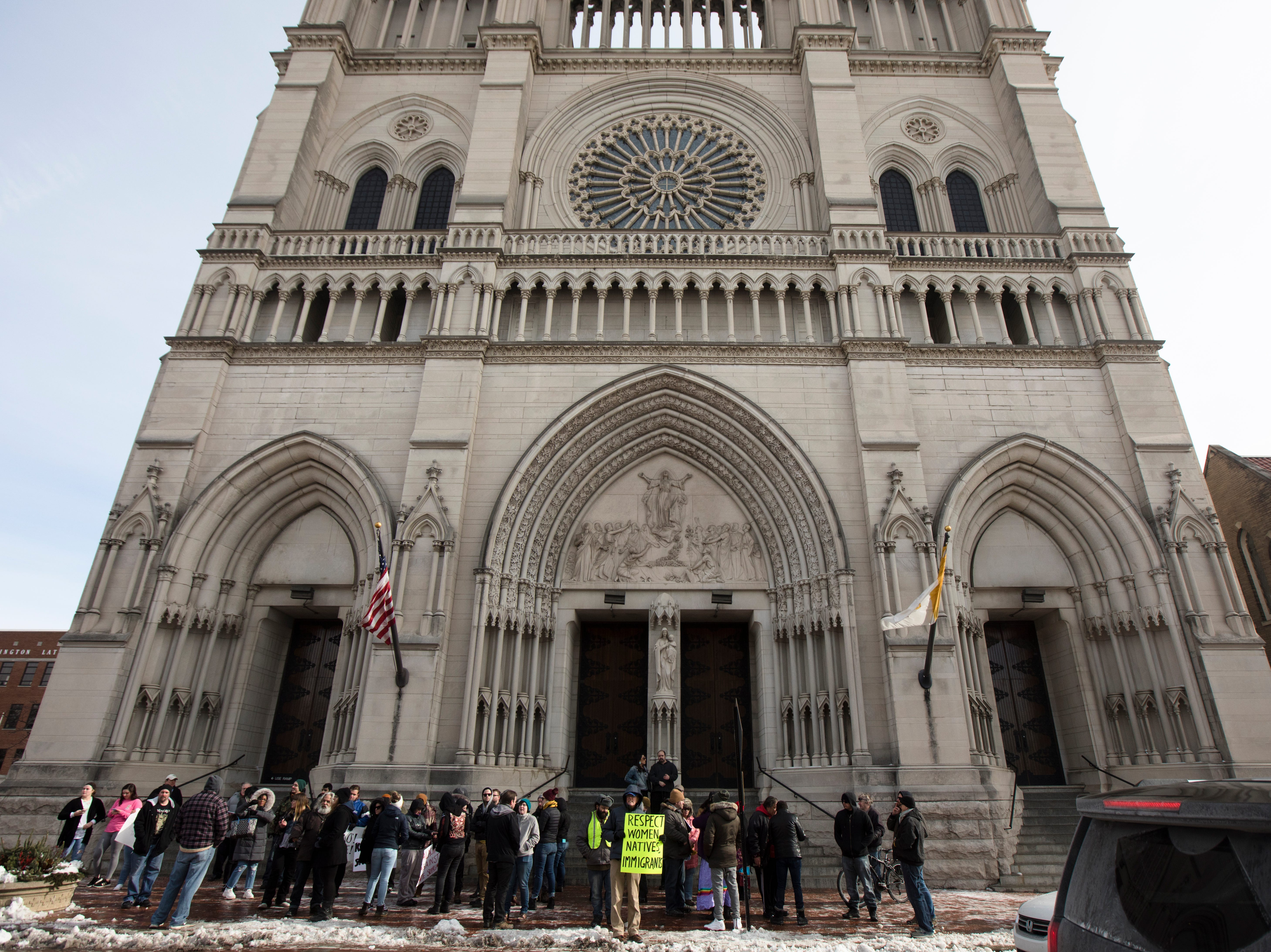 People stand outside the Cathedral of the Assumption during a protest of the Catholic Diocese of Covington outside in Covington, Kentucky, on Tuesday, Jan. 22, 2019.  The protest was planned by the American Indian Movement in response to incident in Washington DC when students of Covington Catholic High School were filmed in an altercation with a Native American man.