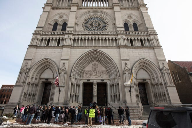 People stand outside the Cathedral of the Assumption in late January during a protest of the Catholic Diocese of Covington in Covington, Kentucky. This week, the diocese filed a federal lawsuit claiming an eponymous, unofficial Facebook page violates copyright law.