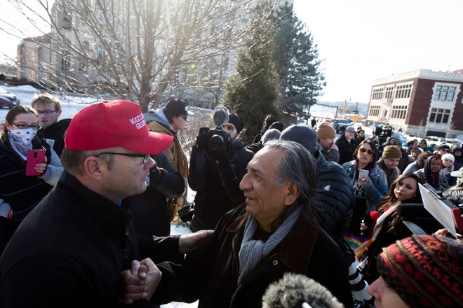 Guy Jones, right, A Native American representative, shakes the hand of Don, who refused to give his last name, during a protest of the Catholic Diocese of Covington outside the Diocese of Covington building in Covington, Kentucky, on Tuesday, Jan. 22, 2019.  The protest was planned by the American Indian Movement in response to incident in Washington DC when students of Covington Catholic High School were filmed in an altercation with a Native American man.