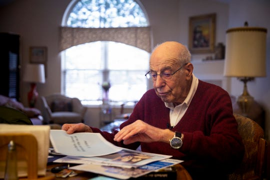 Dr. Al Miller, 96, looks through old photos at his kitchen table table in his Mason home Thursday, January 17, 2019. Miller, a Jewish German, fled Nazi Germany as a boy.  He enlisted in the United States Army and served in Germany after World War II as an interrogator.