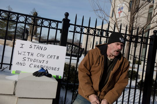 A man who declined to give his name yells back at a person on the street while preparing to hold a sign in support of Covington Catholic students and chaperones outside the Diocese of Covington building in Covington, Kentucky, on Tuesday, Jan. 22, 2019.  The protest was planned by the American Indian Movement in response to incident in Washington DC when students of Covington Catholic High School were filmed in an altercation with a Native American man.