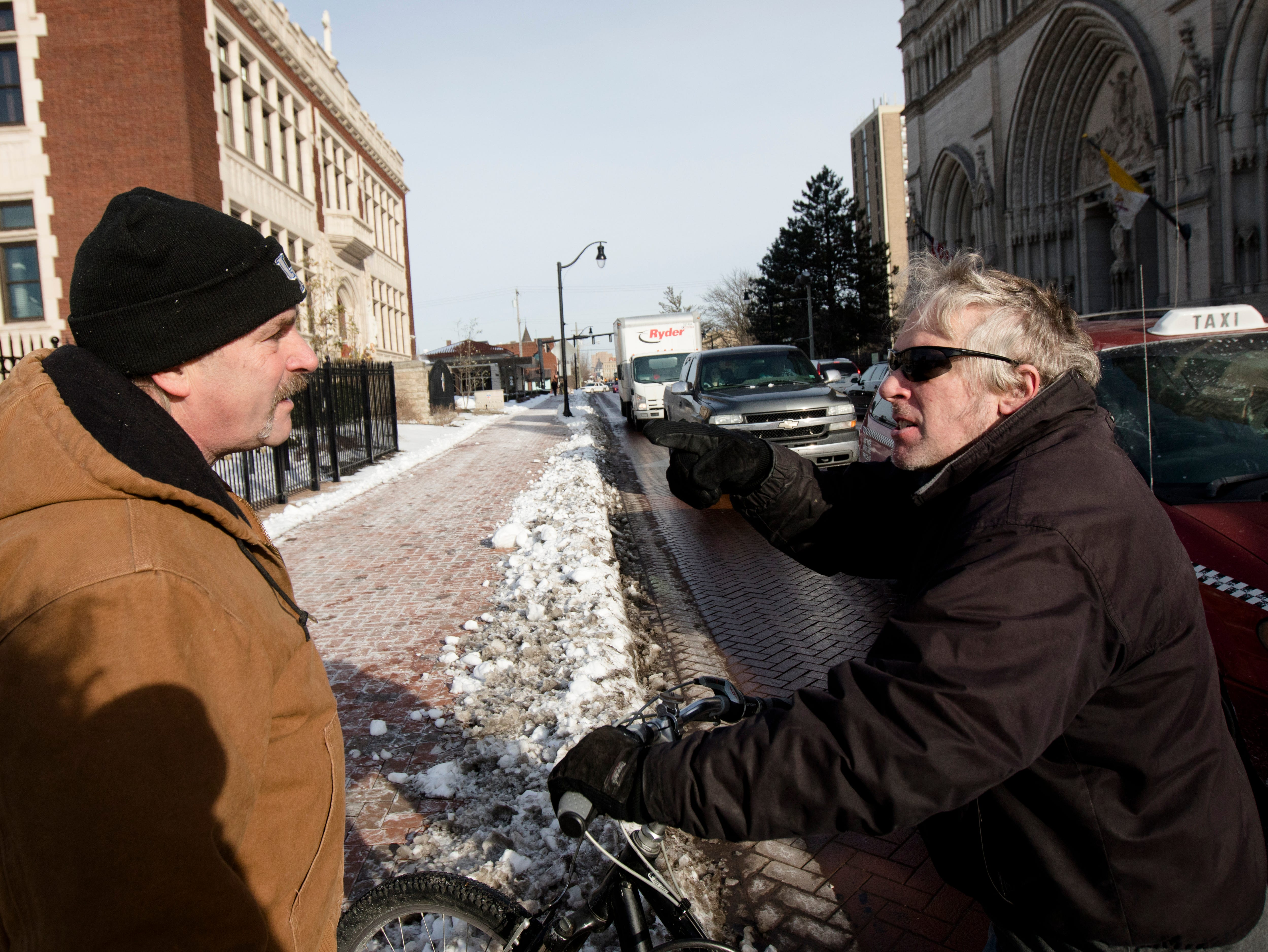 Tim Brown, right, gets into a verbal altercation with a man who declined to give his name yells back at a person on the street while preparing to hold a sign in support of Covington Catholic students and chaperones outside the Diocese of Covington building in Covington, Kentucky, on Tuesday, Jan. 22, 2019.  The protest was planned by the American Indian Movement in response to incident in Washington DC when students of Covington Catholic High School were filmed in an altercation with a Native American man.