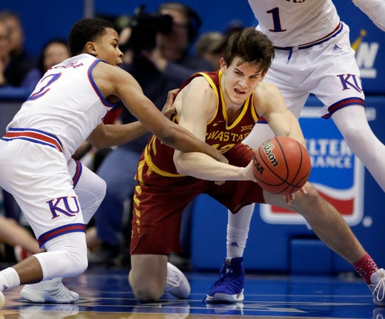 Iowa State forward Michael Jacobson (12) passes to a teammate while covered by Kansas guard Charlie Moore (2) during the first half of an NCAA college basketball game in Lawrence, Kan., Monday, Jan. 21, 2019.