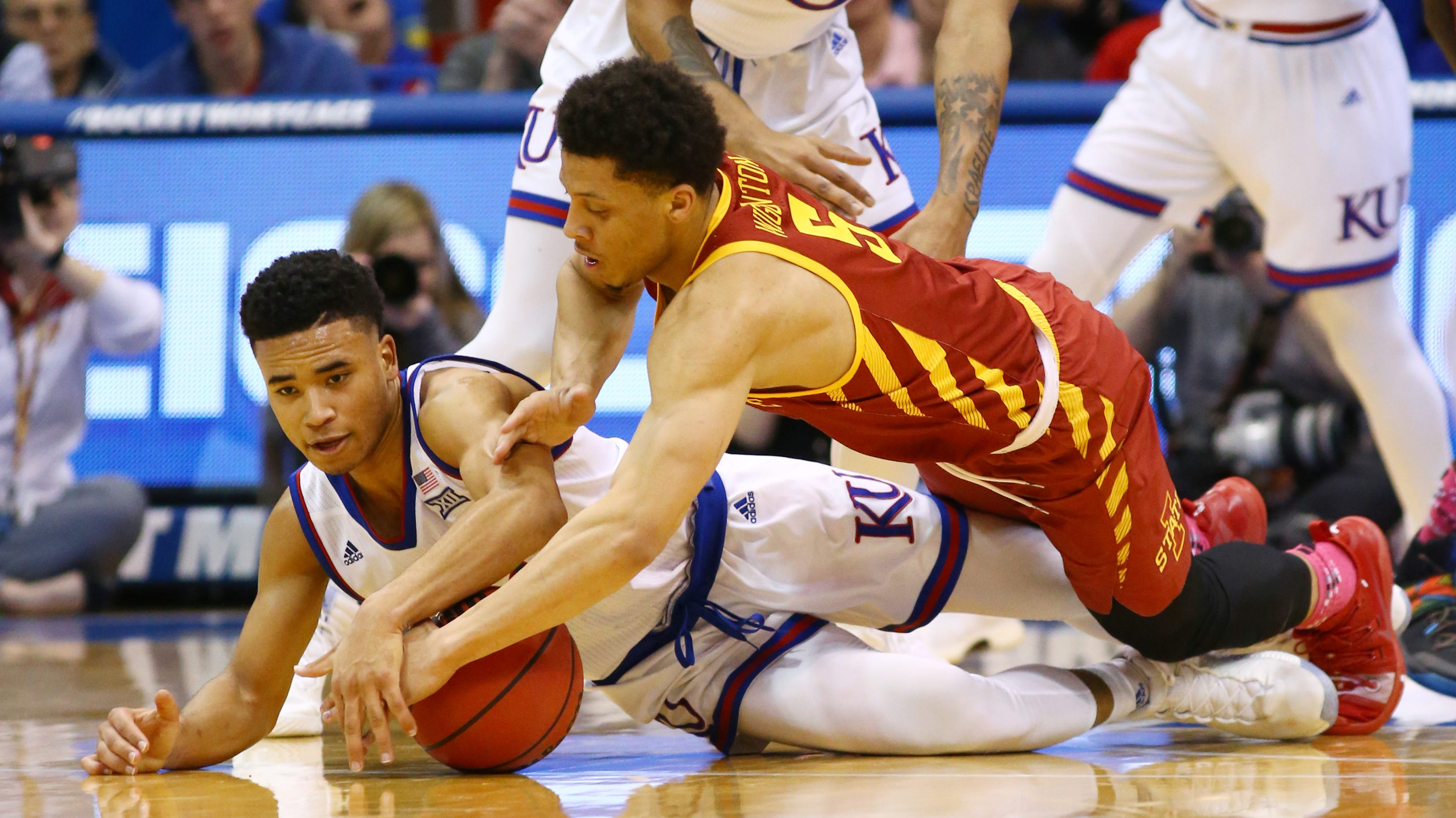 Kansas forward Dedric Lawson (1) and Iowa State guard Lindell Wigginton (5) dive for a loose ball in the second half of their game at Allen Fieldhouse in Lawrence, Kansas, on Monday, Jan. 21, 2019