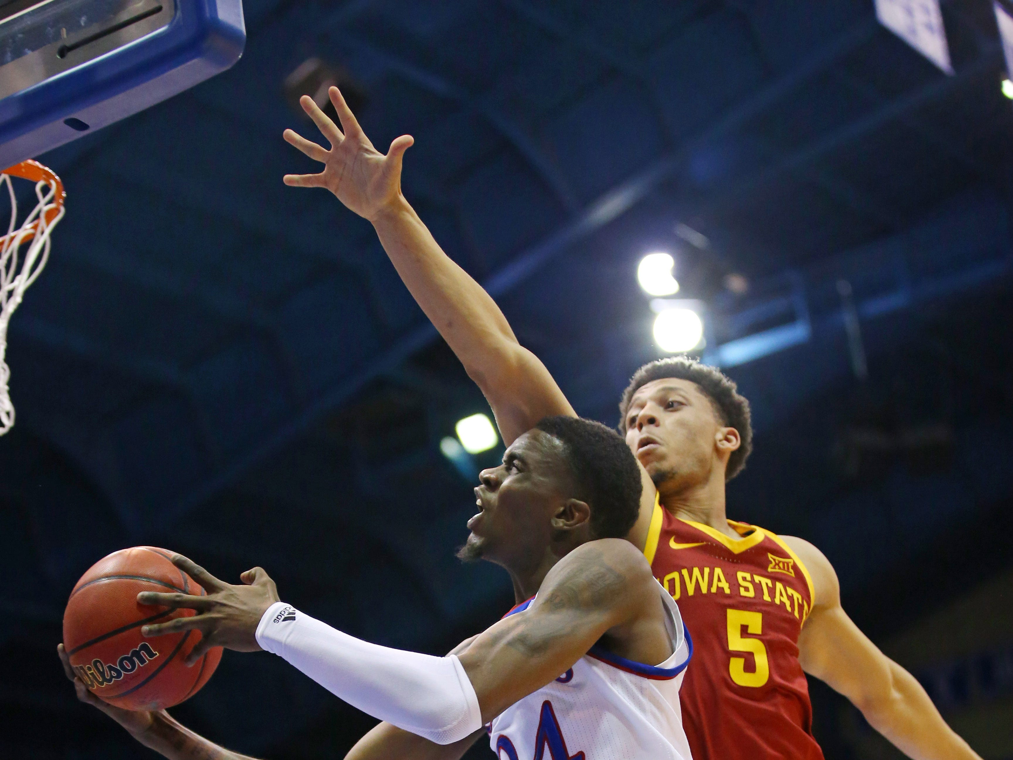 Kansas guard Lagerald Vick (24) goes up for a shott as Iowa State guard Lindell Wigginton (5) defends in the second half of their game at Allen Fieldhouse in Lawrence, Kansas, on Monday, Jan. 21, 2019.