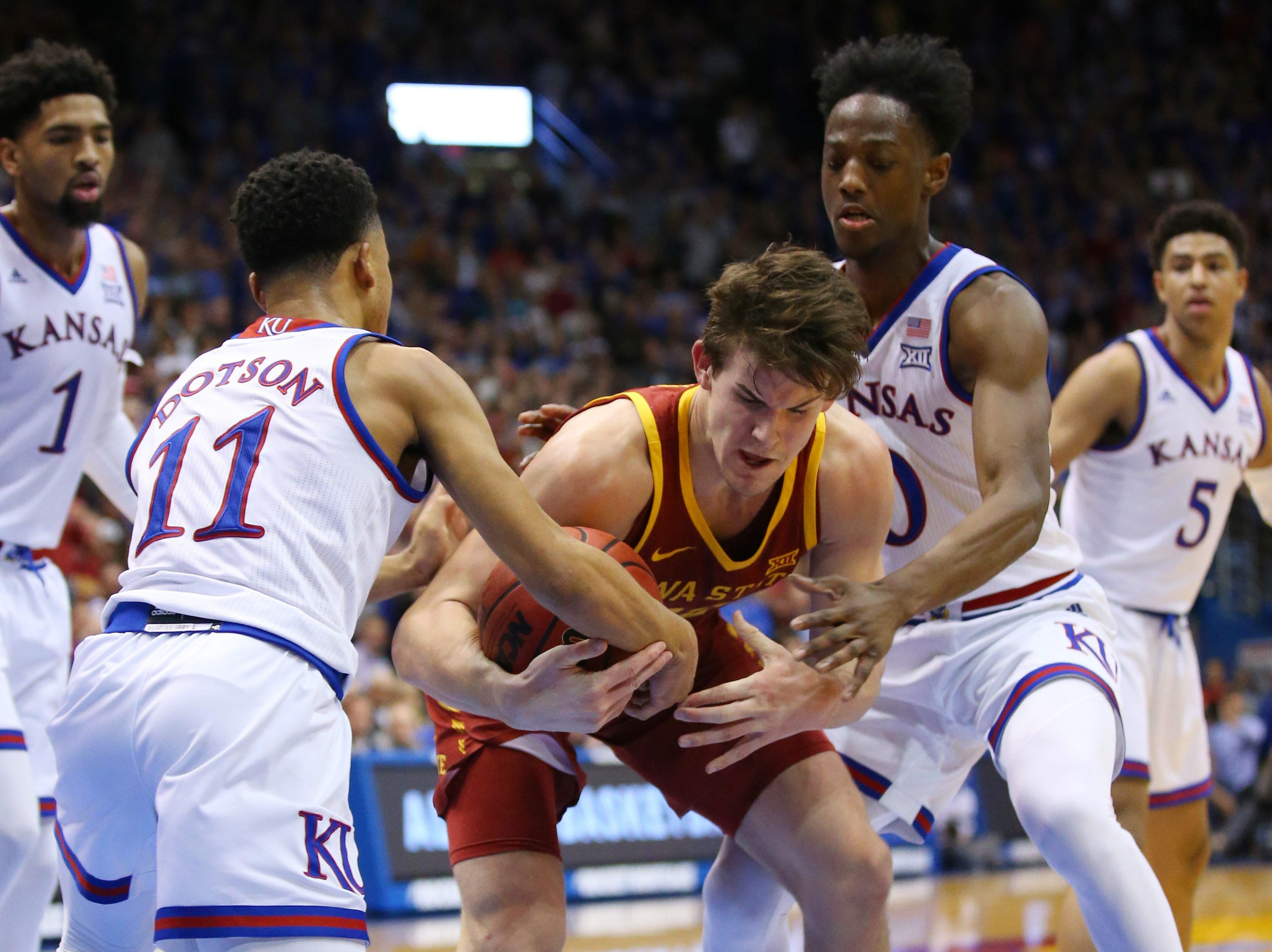 Iowa State Cyclones forward Michael Jacobson (12) fights for the ball with Kansas Jayhawks guard Devon Dotson (11) and guard Marcus Garrett (0) in the first half at Allen Fieldhouse.
