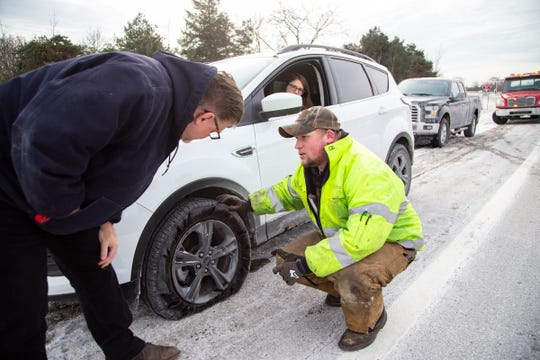 Isabella Huetter, 20, of Fraser sits in her car on the Crooks Road off ramp in Troy as her father Mark Huetter speaks with Byer Wrecker tow driver Austin Sturm about what to do with the shredded tire on Huetter's 2017 Ford Focus. Isabella was on her way to Oakland University when she hit a pothole in the middle lane of I-75 on Tuesday, Jan. 22, 2019.