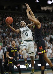 Michigan State guard Cassius Winston scores against Maryland guard Aaron Wiggins during second-half action Monday, January 21, 2019 at the Breslin Center in East Lansing, Mich.