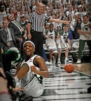 Cassius Winston celebrates an acrobatic shot that went in and draws a foul as the Spartans bench celebrates in Michigan State's 69-55 victory over Maryland Monday at the Breslin Center.