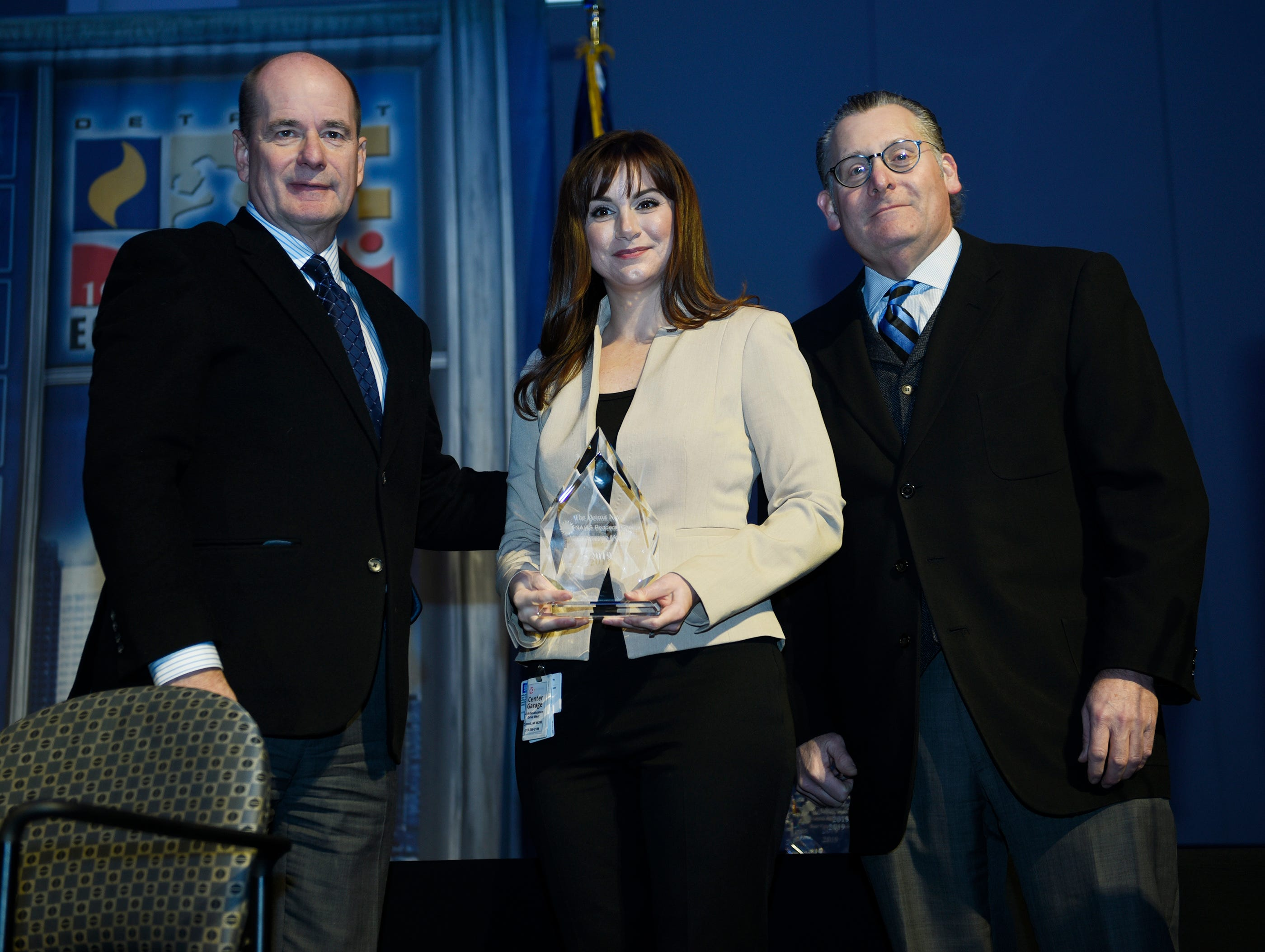Tara Kuhnen of Cadillac accepts her award for Most Amazing Mobility: Cadillac CT6 from Detroit News Editorial Page Editor Nolan Finley, left, and Business Columnist Daniel Howes during the Peoples' Choice award ceremony at Cobo Center.