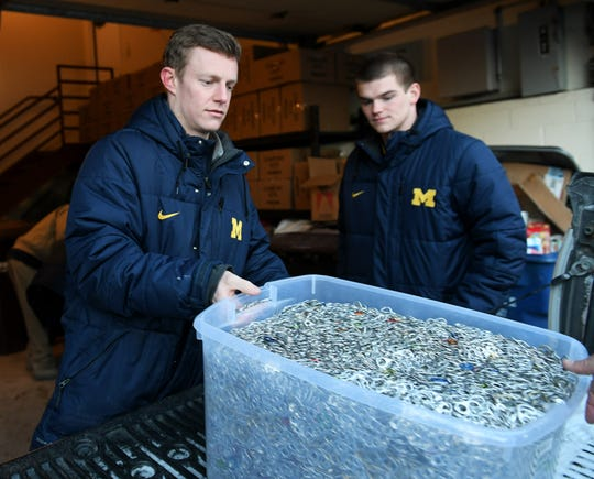 From left, Michigan baseball players Jimmy Kerr, 21, and Ben Keizer, 21, unload bins and boxes filled with pull tabs at the Ronald McDonald House in Ann Arbor.