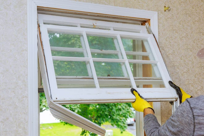 A man removes an old window in order to replace it in a home improvement project. (Dreamstime/TNS)