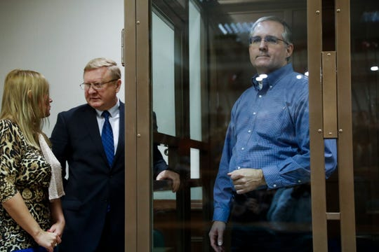Paul Whelan, a former U.S. Marine, who was arrested in Moscow at the end of last year, right, looks through a cage's glass as his lawyers talk to each other in a court room in Moscow, Russia, Tuesday, Jan. 22, 2019.