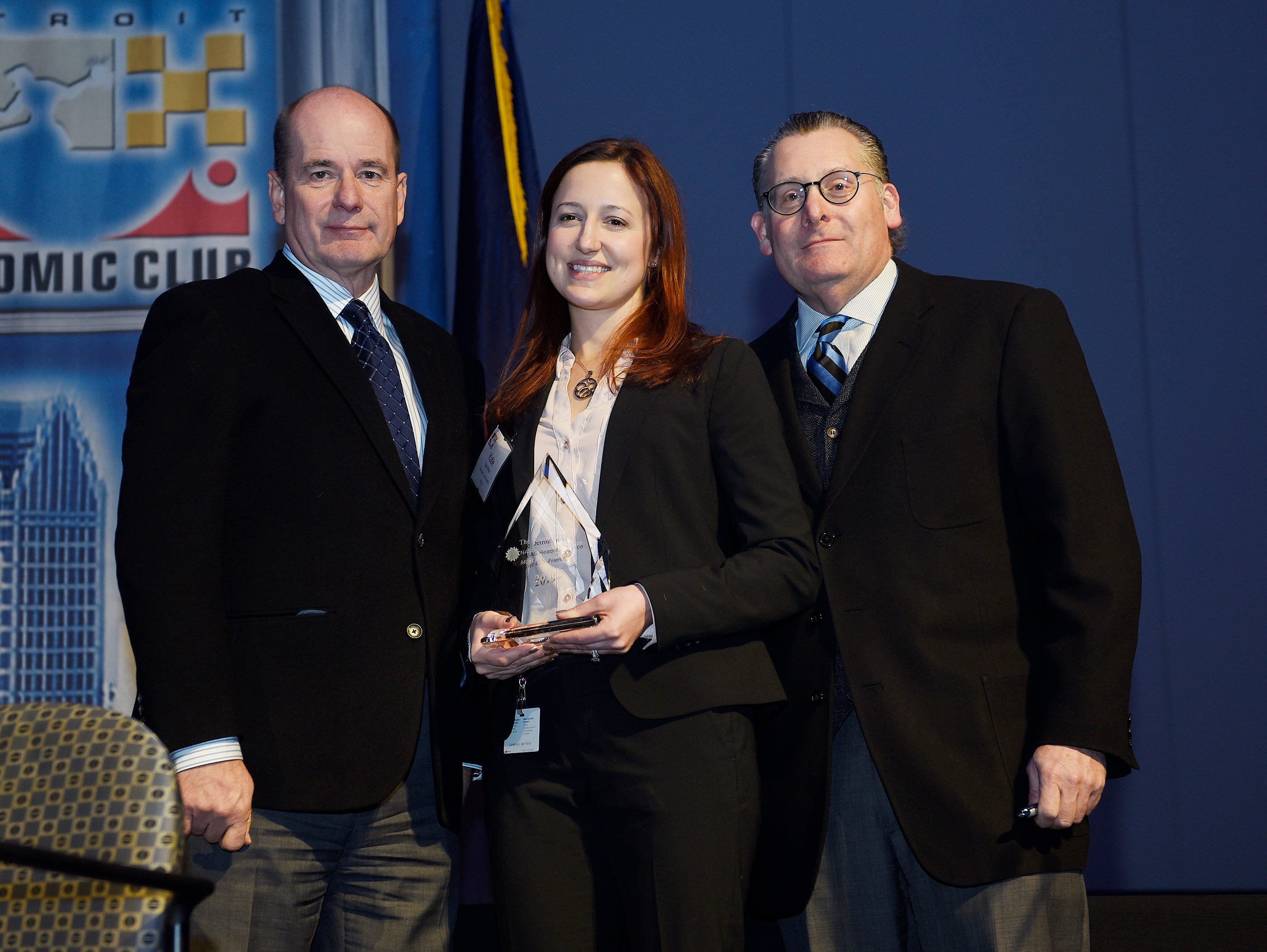 Katie Minter of Chevrolet accepts her award for Most Eco Friendly: Chevy Bolt ev from Detroit News Editorial Page Editor Nolan Finley, left, and Business Columnist Daniel Howes.