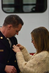 Windsor Severance Fire Rescue Chief Kris Kazian's wife, Kristy Kazian, pins his new badge on his uniform after taking the oath of office Wednesday, Jan. 16, 2019.