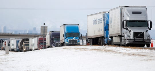 Tractor-trailers are stacked up along the shoulder of eastbound Interstate 70 near the Airpark road exit Tuesday, Jan. 22, 2019, in Aurora, Colo. A winter storm is packing high winds, which has forced the closure of the interstate east from Denver to the state's border with Kansas because of drifting snow and left travelers stranded along the corridor. (AP Photo/David Zalubowski)