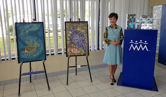 Yeon Sook Park stands beside her artwork on Dec. 31, 2018 at Guam Council of the Arts and Humanities Agency (CAHA) mini-exhibit at Community First Federal Credit Union, Dededo.