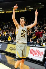 Iowa forward Nicholas Baer gestures to the home crowd after the Dec. 6 win against Iowa State. The Hawkeyes are 3-0 when wearing their alternative gray uniforms this season, having beaten UConn, Iowa State and Nebraska.