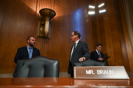 Senator Mike Braun, R-Indiana, first to arrive for a United States Senate Special Committee on Aging hearing held in the Dirksen Senate office building held to examine fighting elder fraud and speaking with committee staff.