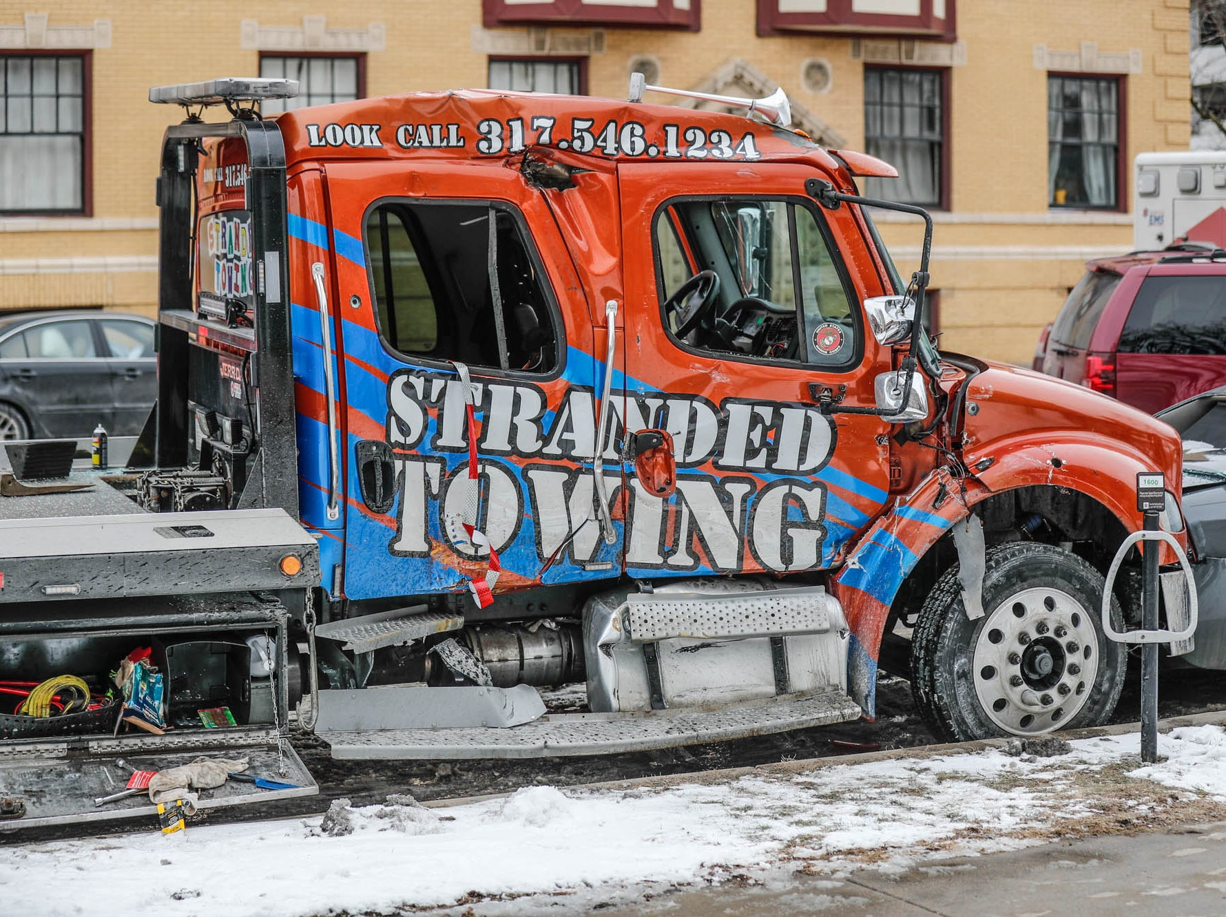 An tow truck collides with parked cars after an M.S.D. of Washington Township Township School Bus collided with the Roberts Park Methodist Church at the corner of Delaware St. and Vermont St. in downtown Indianapolis on Tuesday, Jan. 22, 2019. The bus initially collided with a tow truck after allegedly running a red light, causing the bus to collide with the church and the tow truck to strike parked vehicles along Delaware St. The bus driver and others were transported by ambulance.