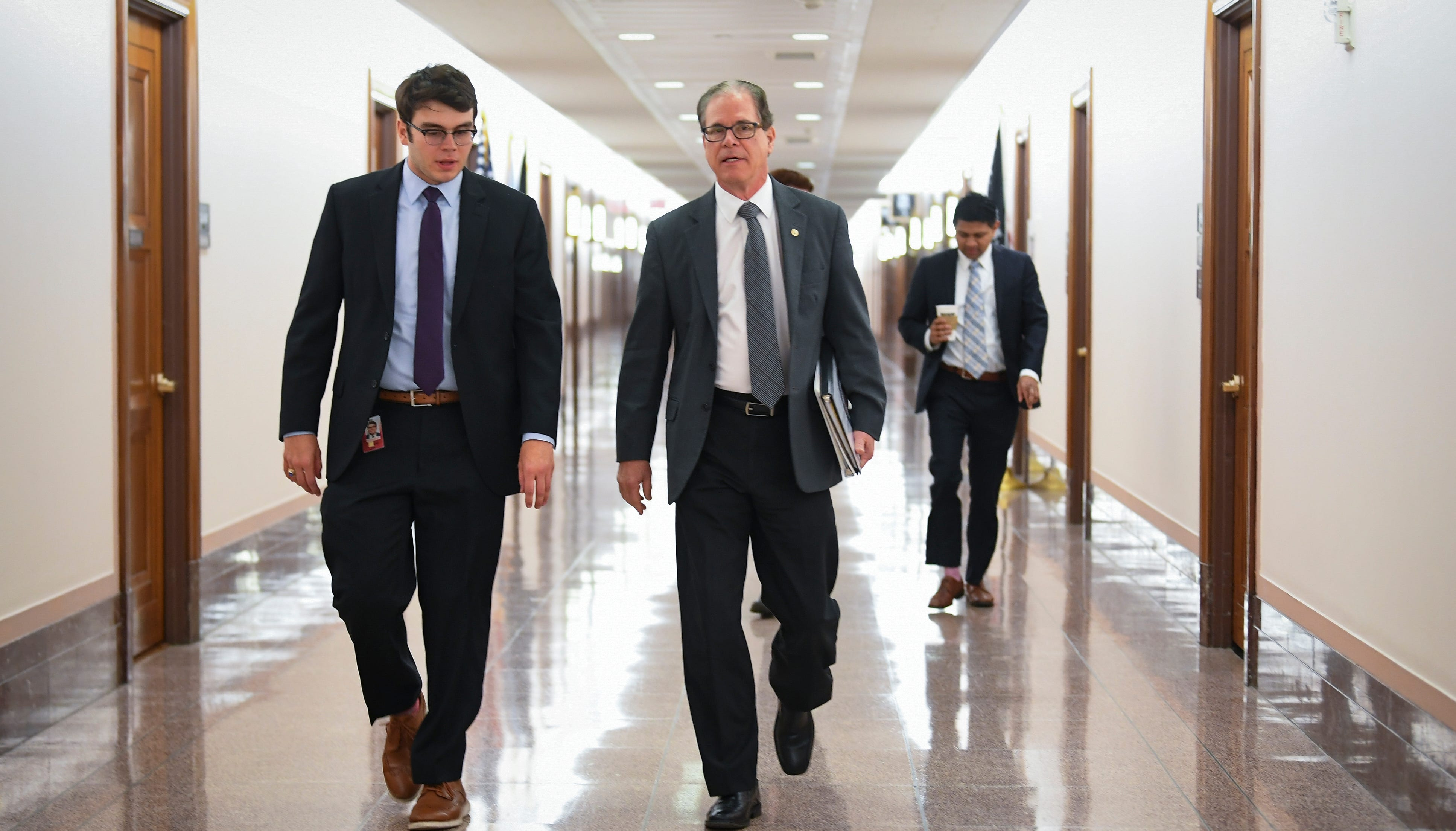Senator Mike Braun, R-Indiana, walking with members of his staff to a United States Senate Special Committee on Aging hearing held in the Dirksen Senate office building examining issue of elder fraud.