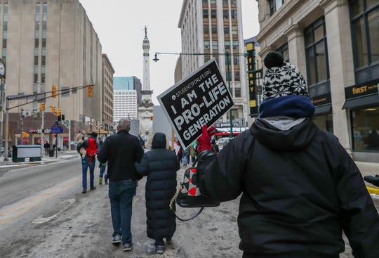 """A large crowd marches down Meridian Street in Indianapolis during the March for Life rally on Tuesday, Jan. 22, 2019. """"We are the pro-life generation,"""" yelled marchers, holding signs that read """"Love Life"""" and Made by God."""""""