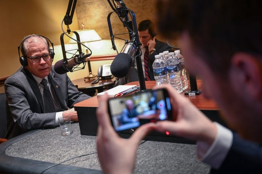 Senator Mike Braun, R-Indiana, on the radio live during early morning radio calls speaking to WOWO Fort Wayne and also with Indianapolis WIBC's Tony Katz from the Senate Recording Studios with Braun's chief of staff Josh Kelley listening on headphones while Zach Riddle, Braun's deputy communication director records the conversations.