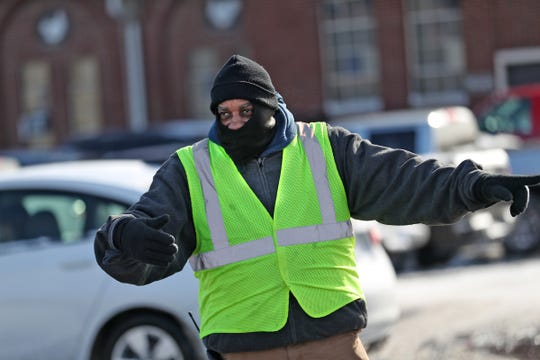 Ira Smith keeps warm as he directs traffic at the Indiana State Fairgrounds on Sunday, Jan. 20, 2019.