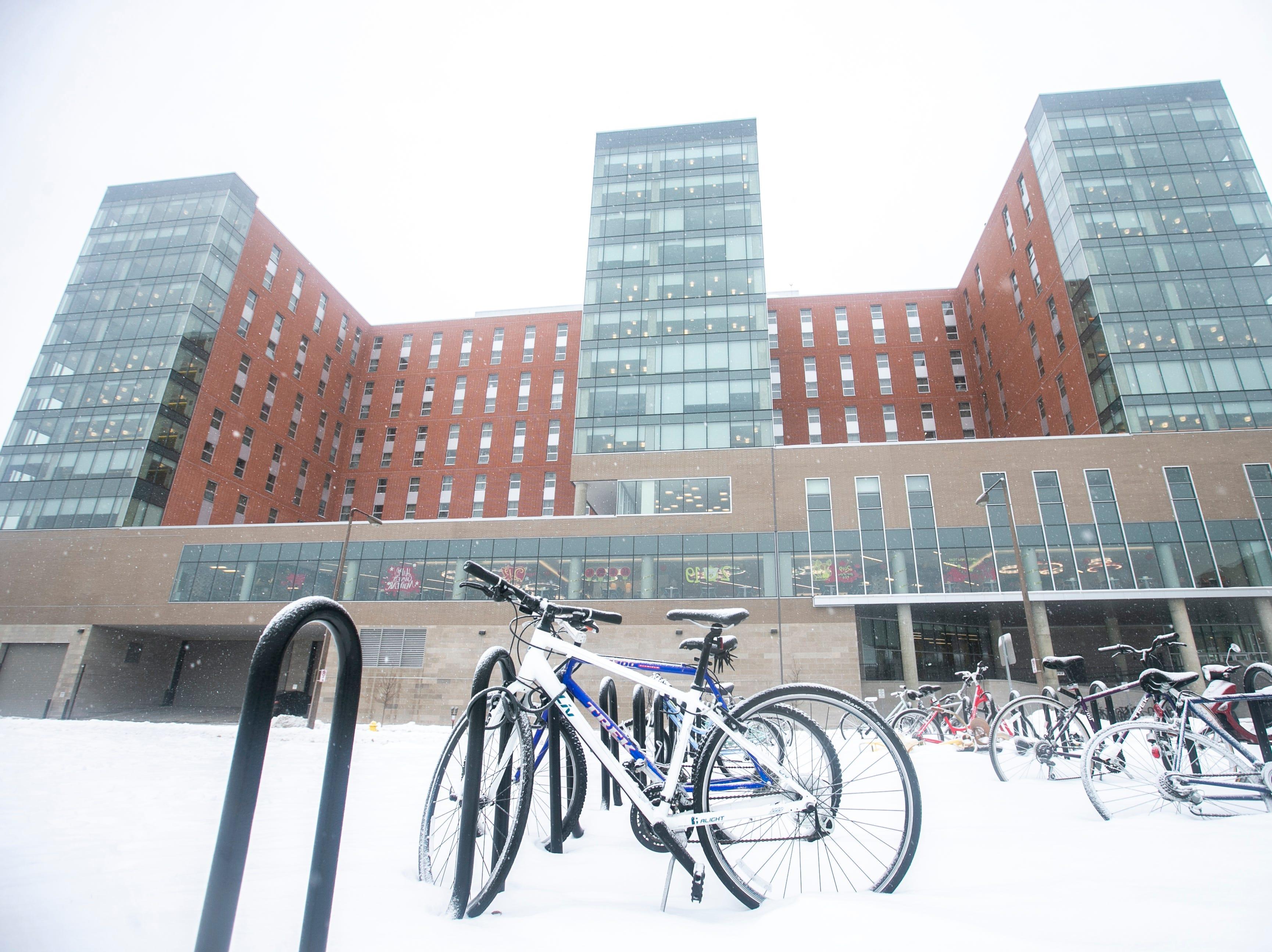 Bikes across from Catlett Residence Hall get covered as light snow falls on Tuesday, Jan. 22, 2019, in Iowa City, Iowa.