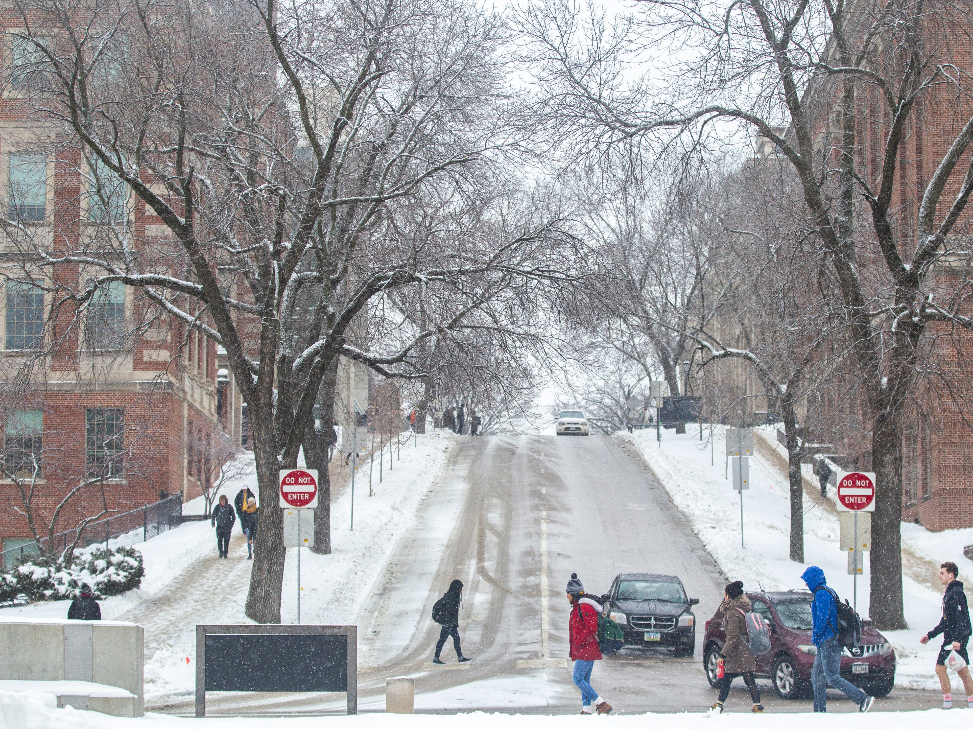 Students walk along Madison Street while cars drive down Market Street as light snow falls on Tuesday, Jan. 22, 2019, in Iowa City, Iowa.