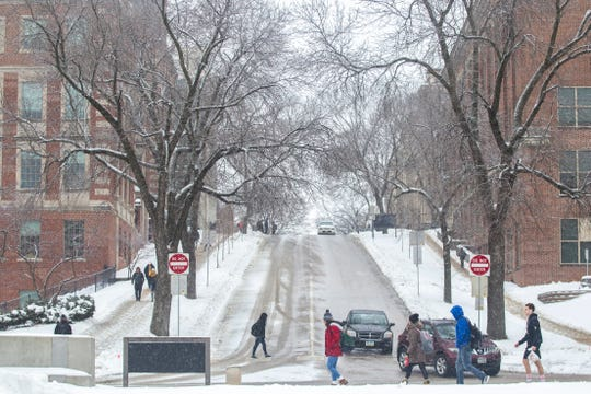 Students walk along Madison Street while cars drive down Market Street as light snow falls on Tuesday, Jan. 22, 2019, in Iowa City, Iowa.