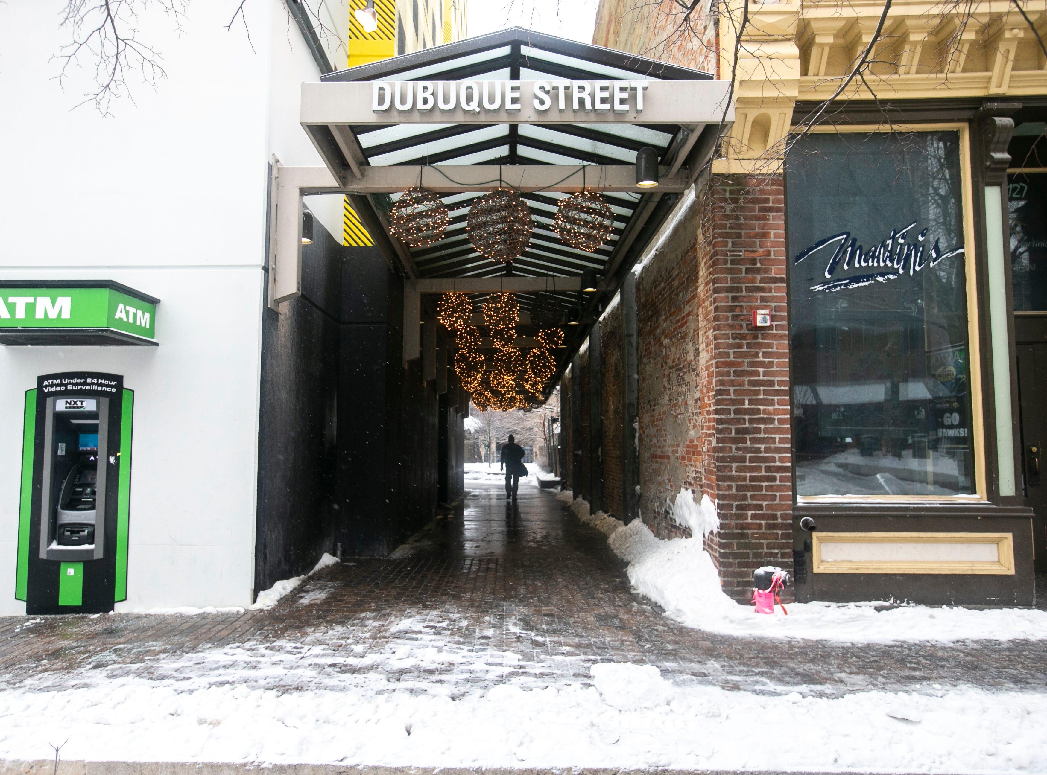 A person walks down a tunnel towards Dubuque Street as light snow falls on Tuesday, Jan. 22, 2019, along the pedestrian mall in Iowa City, Iowa.
