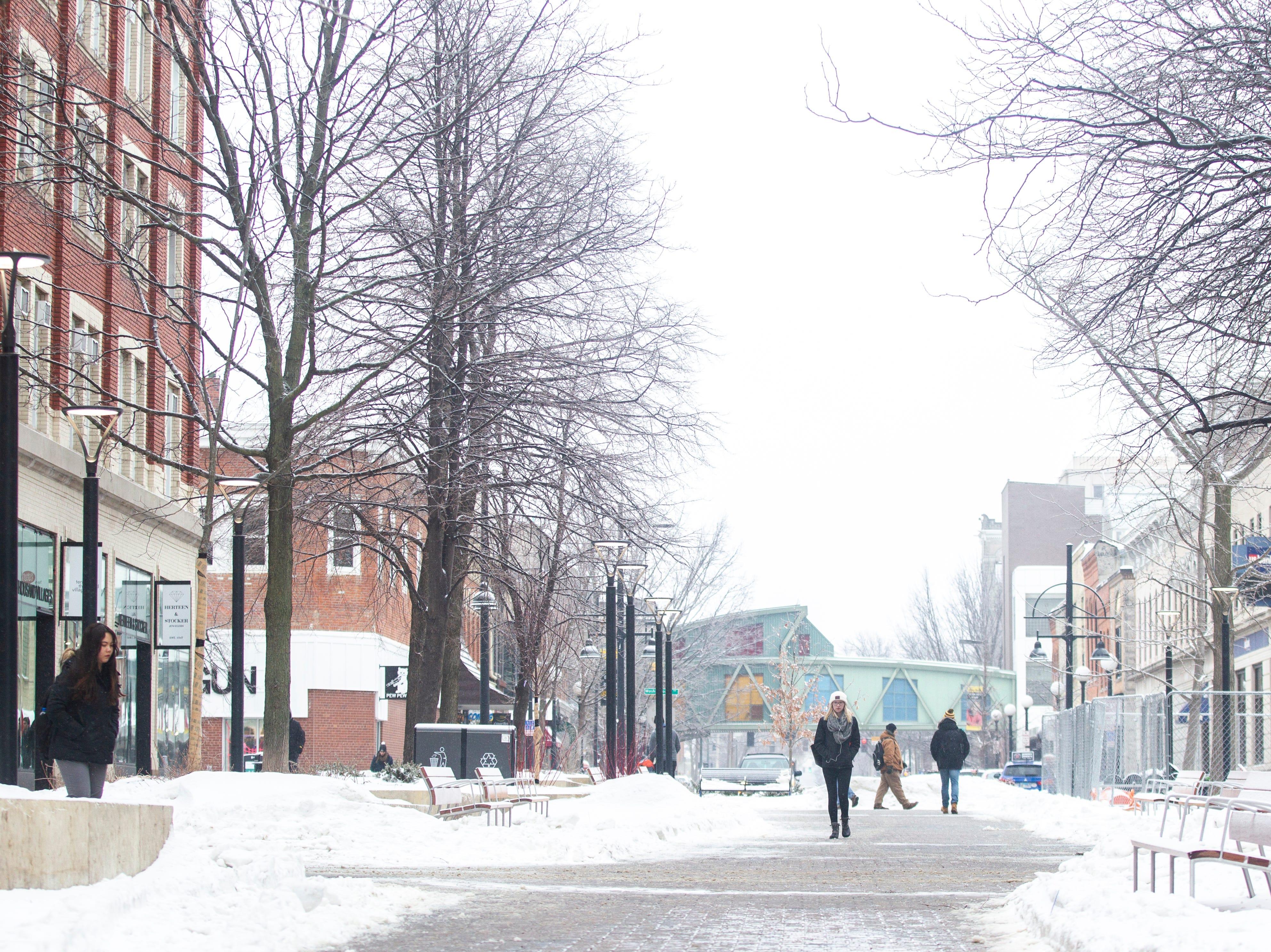 People walk through the pedestrian mall as light snow falls on Tuesday, Jan. 22, 2019, in Iowa City, Iowa.