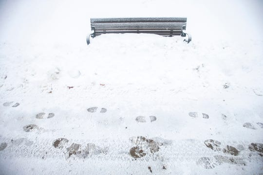 A bench gets packed in as light snow falls on Tuesday, Jan. 22, 2019, in Iowa City, Iowa.