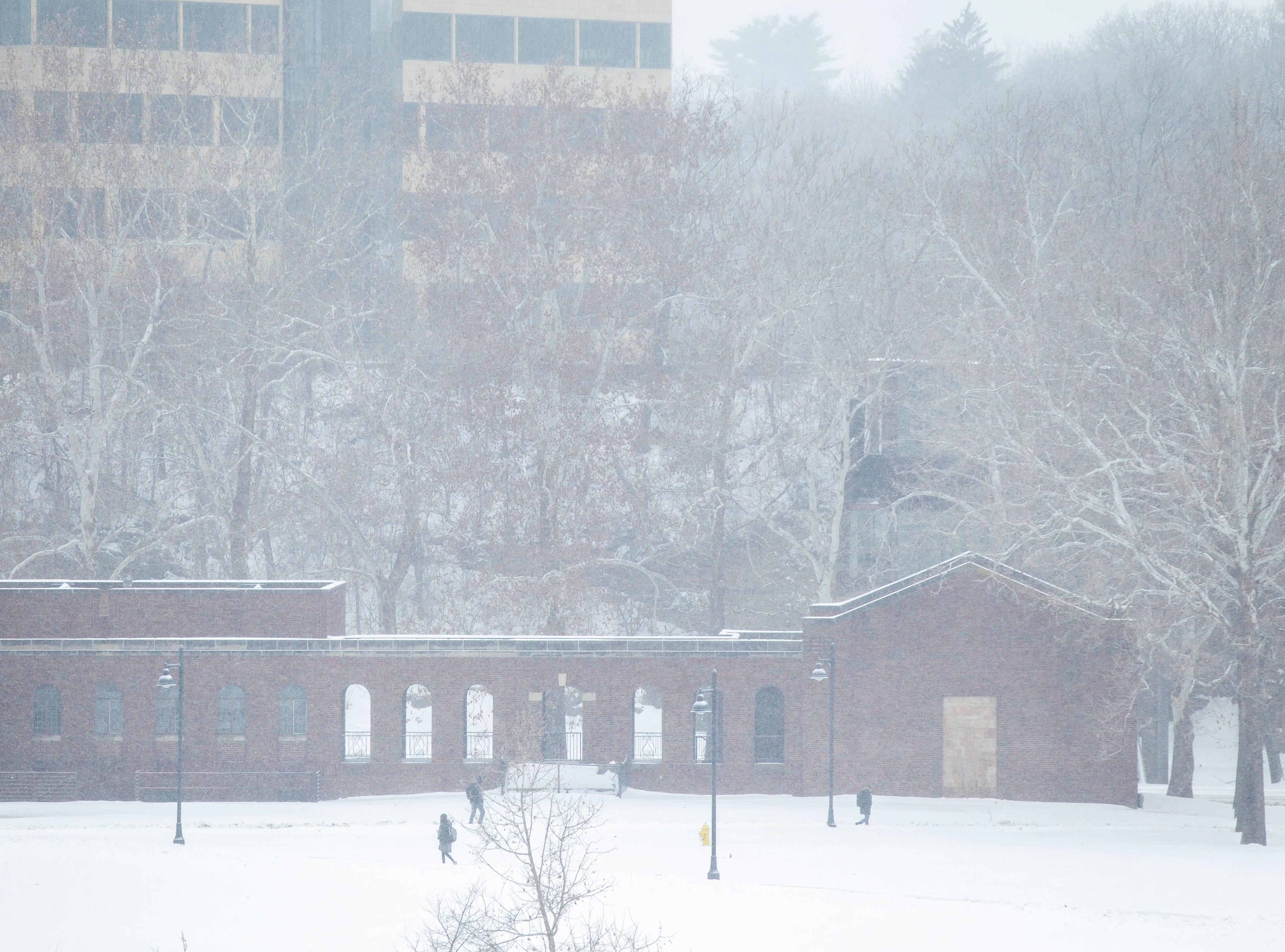 Students walk along the west side of campus as light snow falls on Tuesday, Jan. 22, 2019, in Iowa City, Iowa.