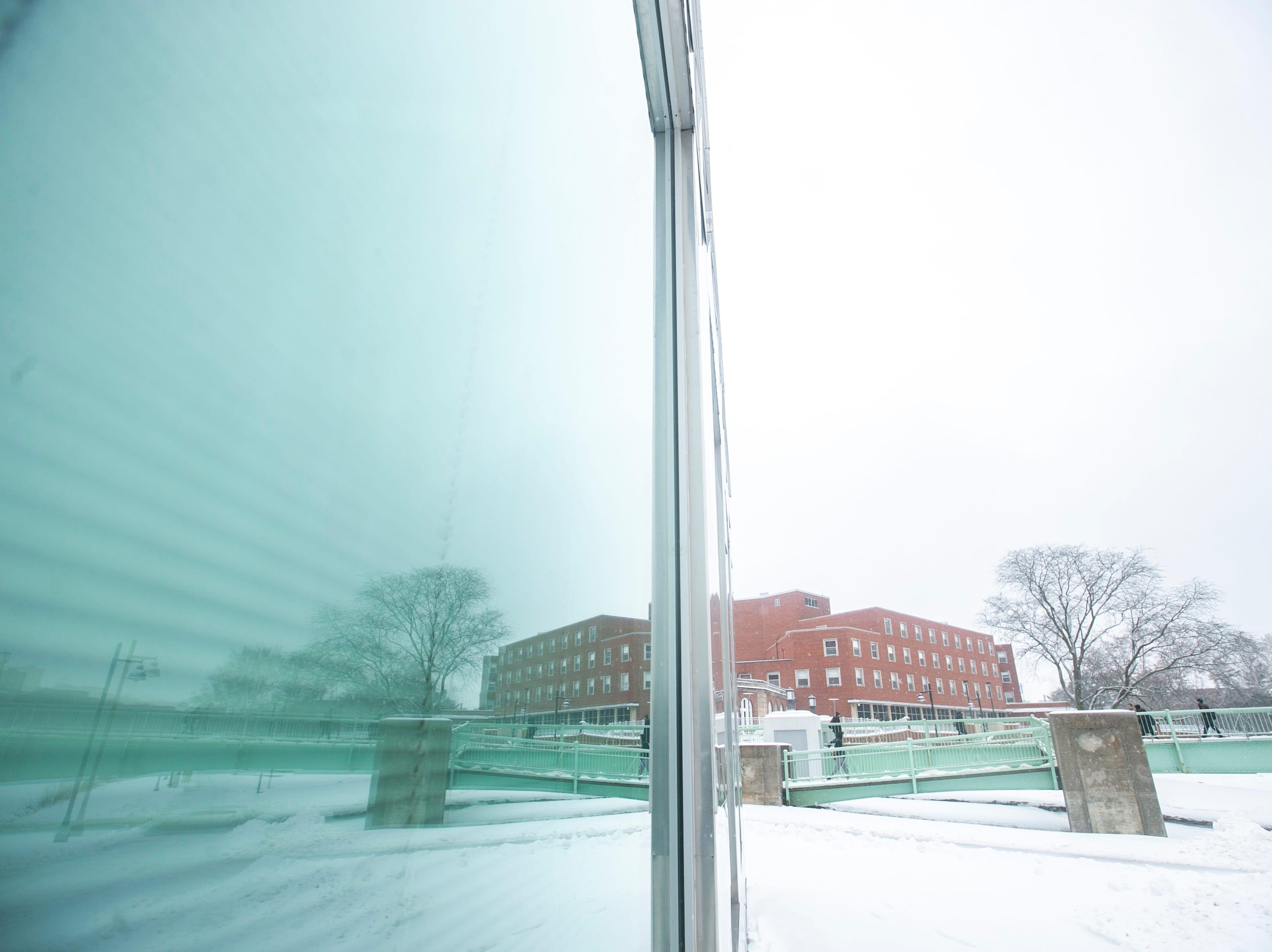 The Iowa Memorial Union bridge is reflected in a window of the Iowa Advanced Technology Laboratories building as light snow falls on Tuesday, Jan. 22, 2019, in Iowa City, Iowa.