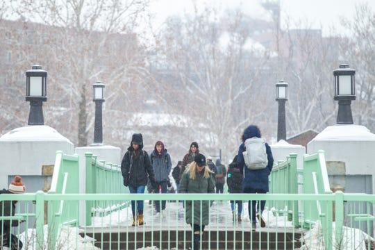 Students cross a bridge near the Iowa Memorial Union as light snow falls on Tuesday, Jan. 22, 2019, in Iowa City, Iowa.